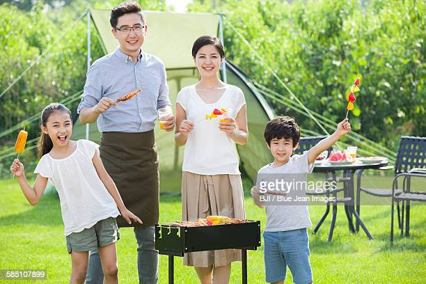 young family barbecuing outdoors - mother and daughter smoking stock photos and pictures