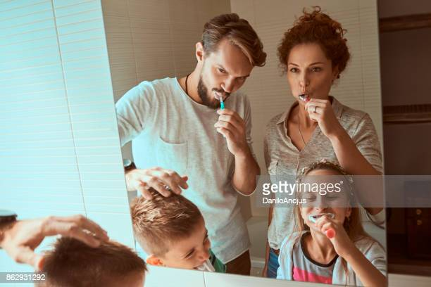young family brushing teeth together
