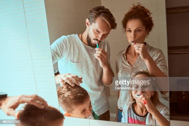 jong gezin samen tandenpoetsen - menselijk gebit stockfoto's en -beelden