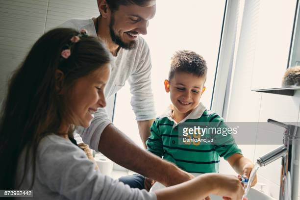 young family having fun together brushing