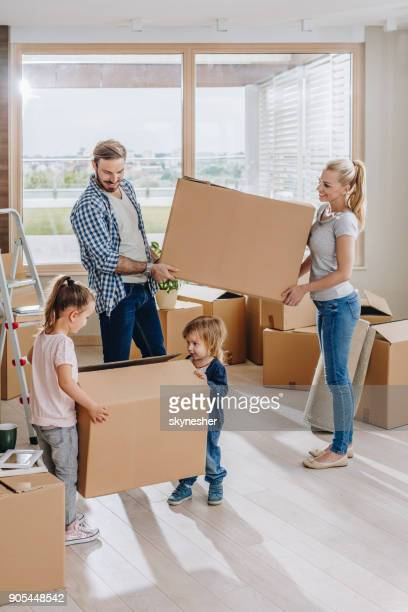 young family carrying their belongings while moving into new penthouse. - penthouse girls stock pictures, royalty-free photos & images