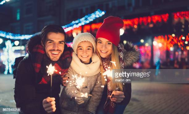 young family celebrating christmas - fete stock photos and pictures