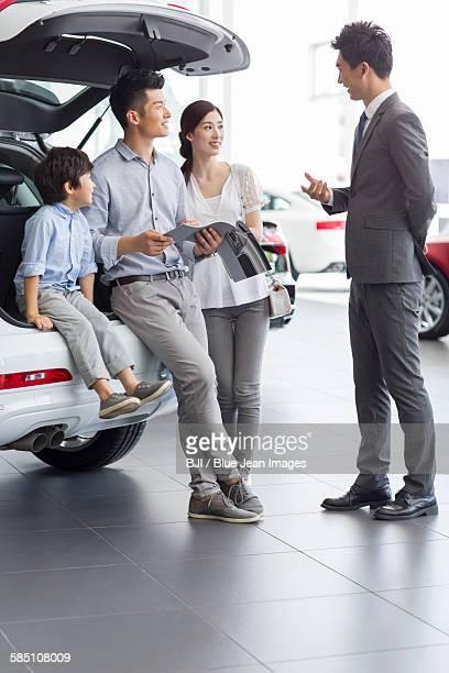 Young family choosing car in showroom