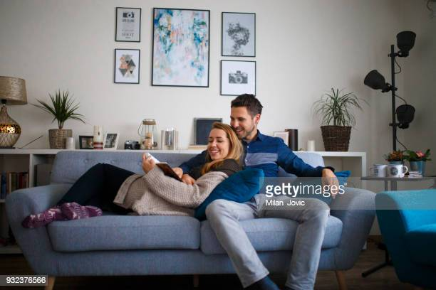 young family couple together at home reading a book - traditionally scandinavian stock pictures, royalty-free photos & images