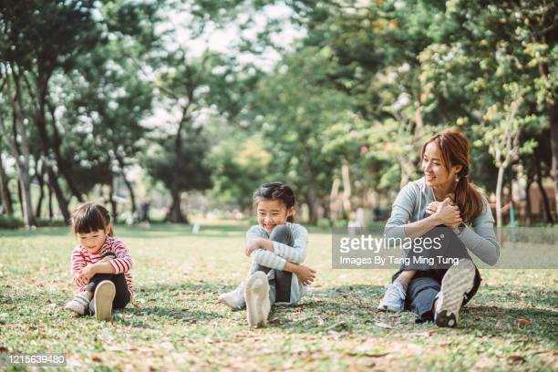 young family doing stretching exercise in park joyfully - physical education stock pictures, royalty-free photos & images