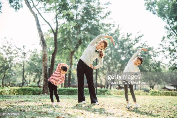 young family doing stretching exercises on the lawn joyfully - affectionate stock pictures, royalty-free photos & images