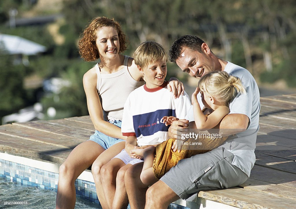 Young family, dressed, sitting on edge of pool. : Stockfoto