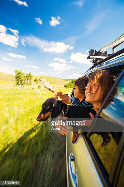 Jeune famille de conduire une voiture dans le champ