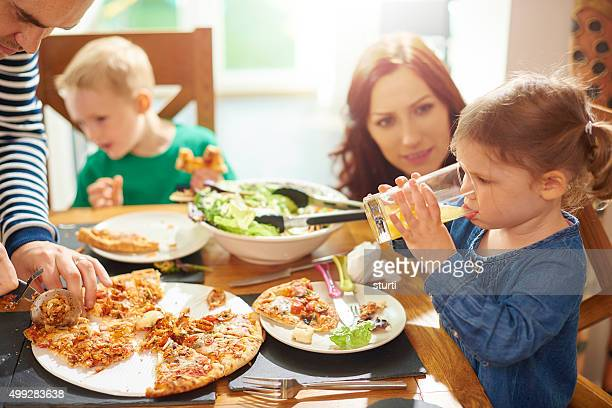 young family eating and drinking at the table