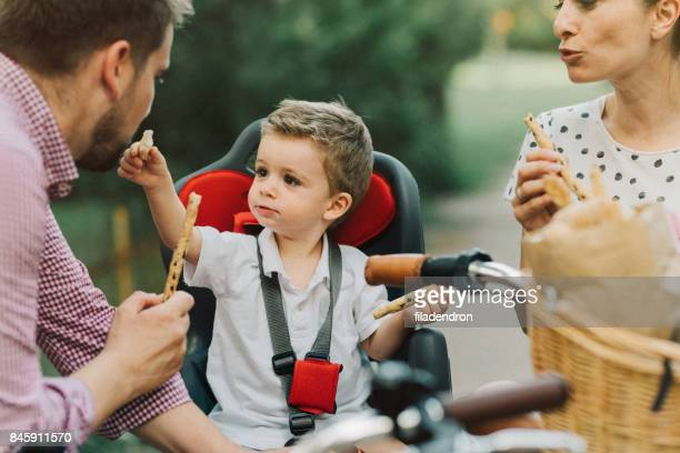 Young family eating breadsticks in the park