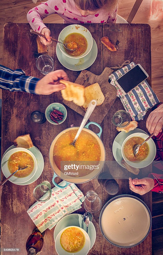 Young Family Eating Chicken Soup With Carrots And Parsnips Stock