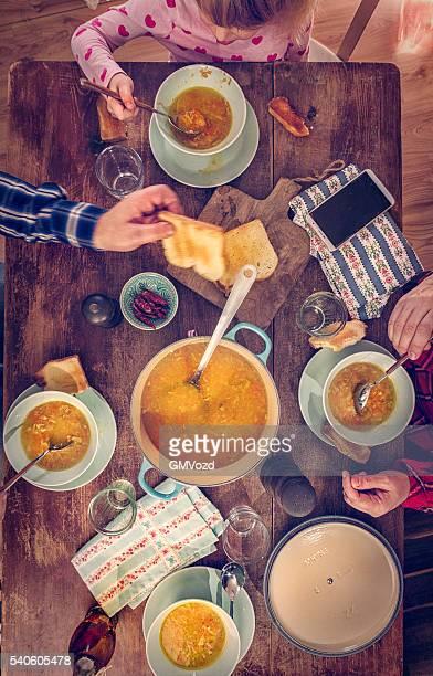 Jovem família comer Sopa de galinha com cenouras e Pastinagas