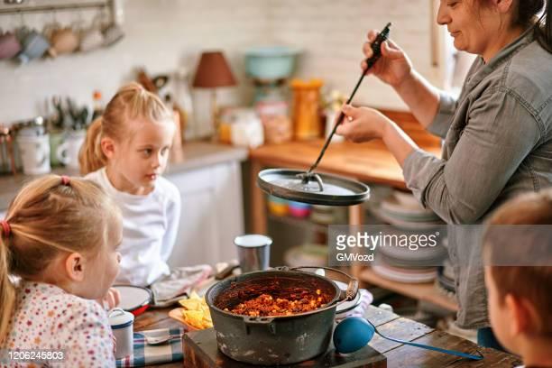チリコンカーンを食べる若い家族 - ダッチオーブン ストックフォトと画像