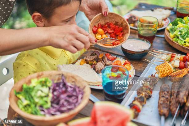 young family eating lamb, beef and vegetable kebab with green salad outside - vegetable kebab stock pictures, royalty-free photos & images