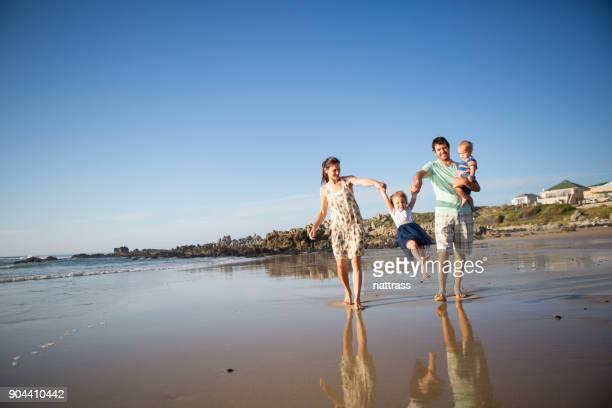 Young family enjoy walking on the beach