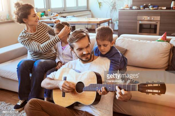 young family enjoying at home and father playing guitar with his son