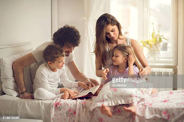 Young family enjoying in bedroom in the morning.