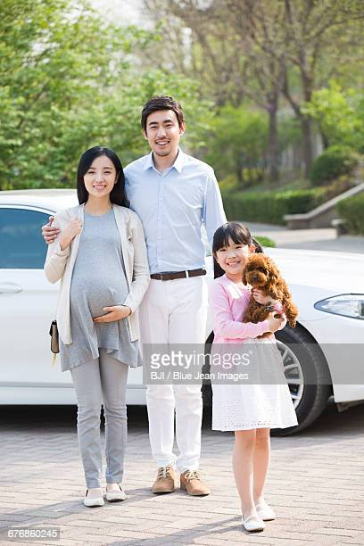 Young family getting out of car with their pet dog