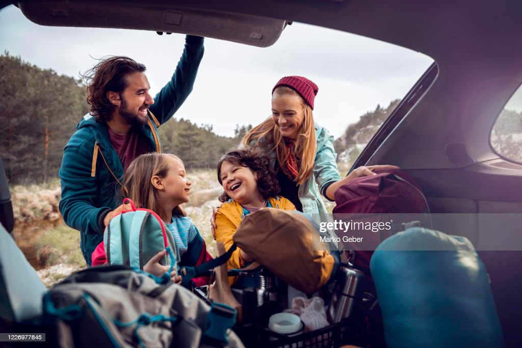 Young family getting the camping supplies out of the car : Stock Photo