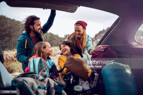 young family getting the camping supplies out of the car - vacanze foto e immagini stock