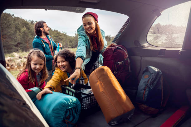 Young family getting the camping supplies out of the car