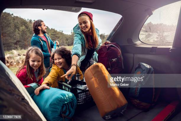 young family getting the camping supplies out of the car - love stock pictures, royalty-free photos & images