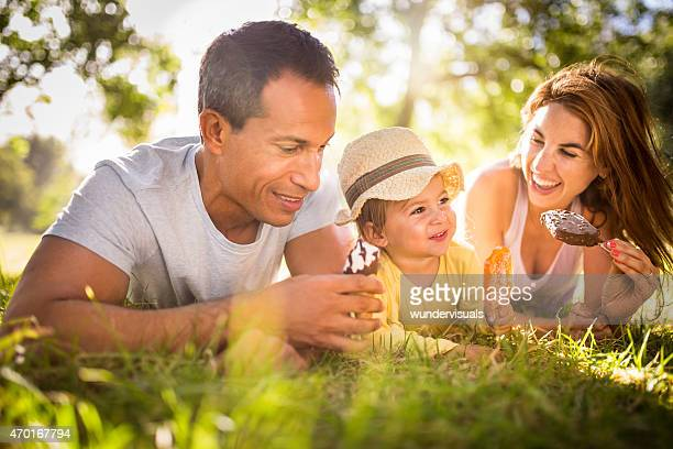 Young family happily eating ice creams together in a park