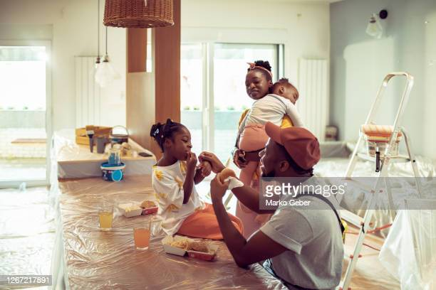young family having a break from painting - family stock pictures, royalty-free photos & images
