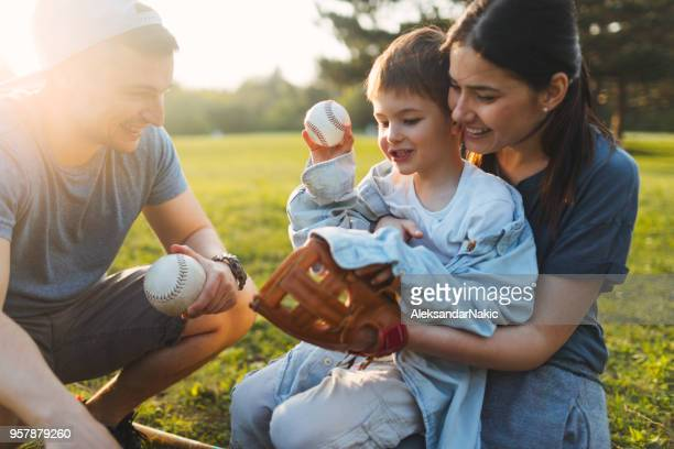 young family having a fun sport day outdoors - baseball mom stock pictures, royalty-free photos & images