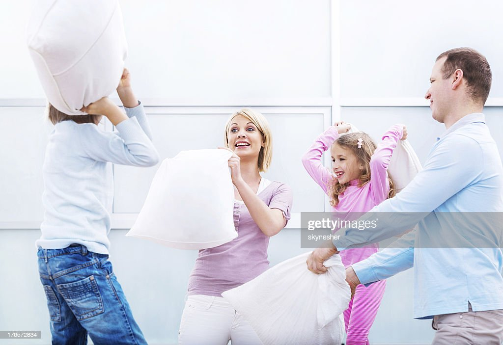 Young family having a pillow fight! : Stock Photo