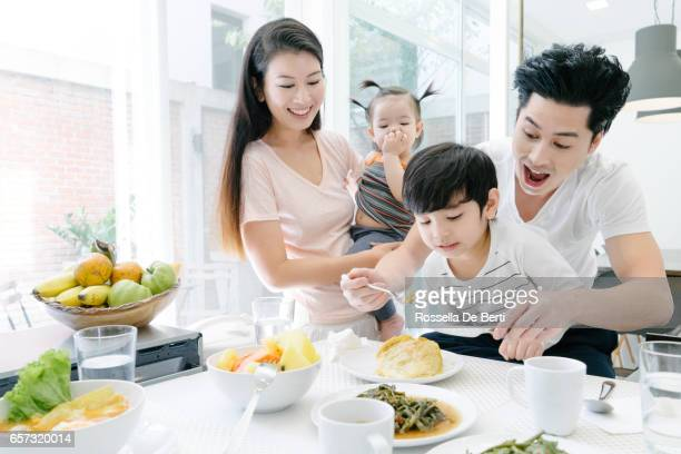 young family having breakfast in the kitchen - east asian culture stock photos and pictures