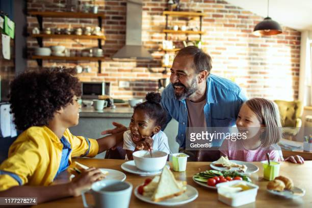 young family having breakfast - adoption stock pictures, royalty-free photos & images