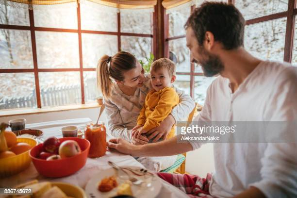 young family having breakfast - winter home stock pictures, royalty-free photos & images