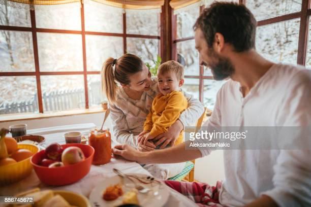 joven familia desayunando - winter family fotografías e imágenes de stock