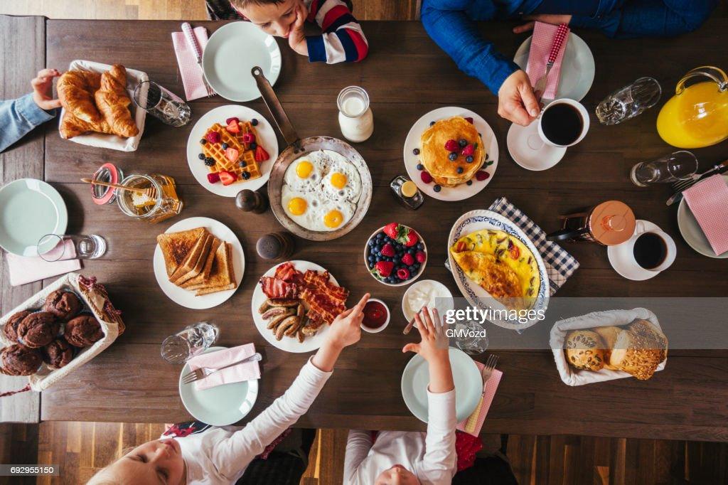 Jovem família tomando café da manhã com ovos, Bacon, iogurte com frutas frescas : Foto de stock