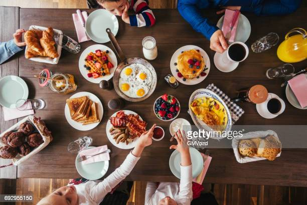 young family having breakfast with eggs, bacon, yogurt with fresh fruits - dinner table stock photos and pictures