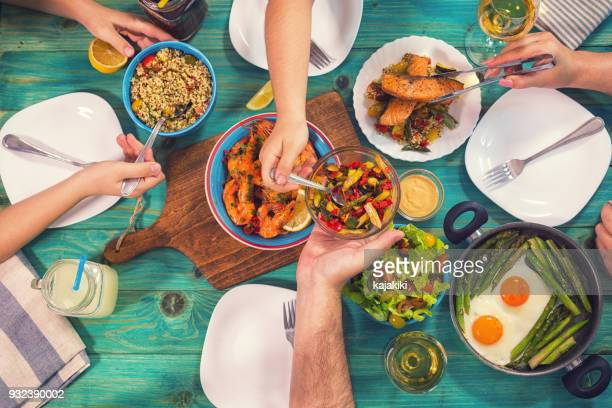 young family having lunch at home - mediterranean food stock pictures, royalty-free photos & images