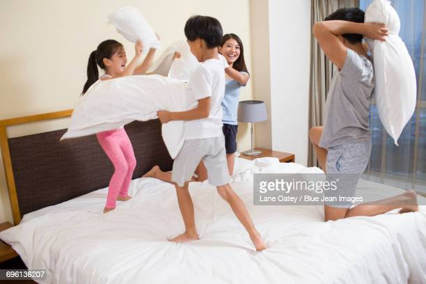 Young family having pillow fight