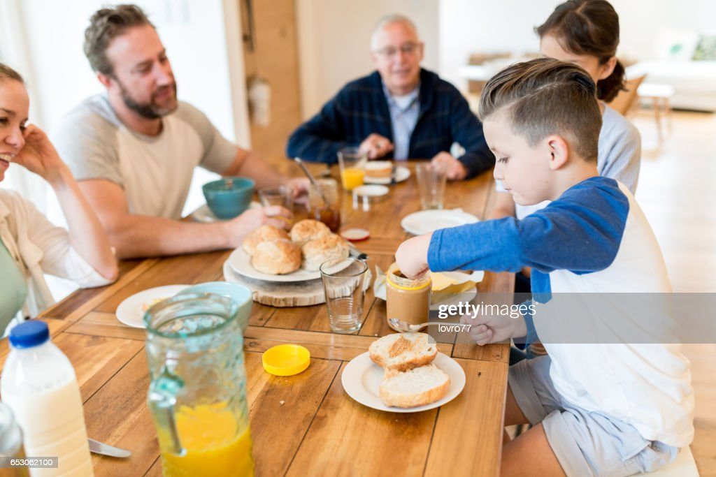 Young family having pleasant conversation during breakfast in the dining room : Stock Photo