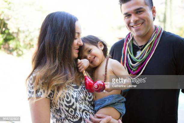 Young family holding smiling toddler in summertime