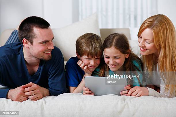 Young family in bed using digital tablet