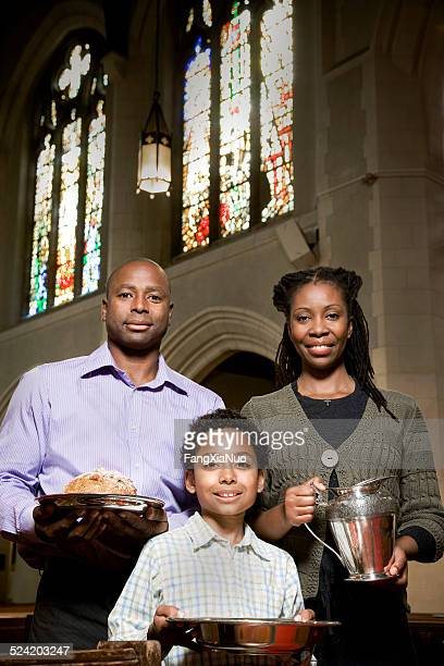 Young Family in Church Aisle With Bread and Wine