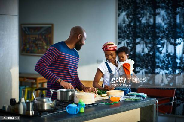 young family in kitchen - black man holding baby stock photos and pictures