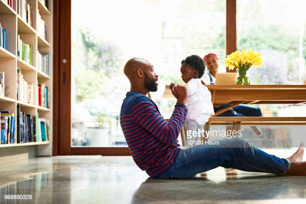 young family in livingroom - twee ouders stockfoto's en -beelden
