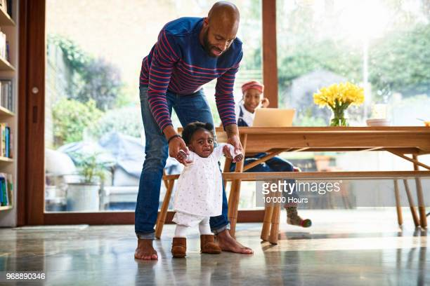 young family in livingroom - bent over babes stock pictures, royalty-free photos & images