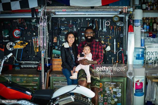 Young family in motorcycle workshop.