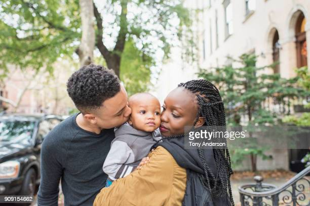 young family in their city neighborhood street - young family stock pictures, royalty-free photos & images