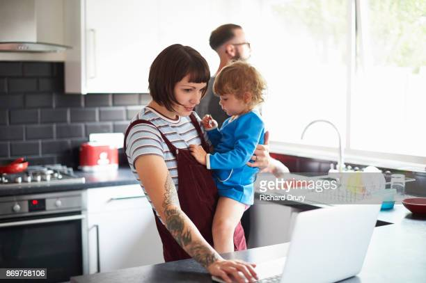 young family in their kitchen - multi tasking stock pictures, royalty-free photos & images