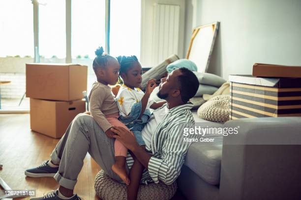 young family in their new home - genderblend stock pictures, royalty-free photos & images