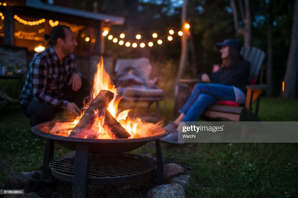Young family is warming near campfire late evening at a beatiful canadian chalet : Stock Photo